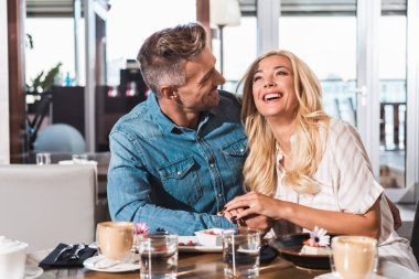 Handsome boyfriend looking at laughing girlfriend at table in cafe stock vector