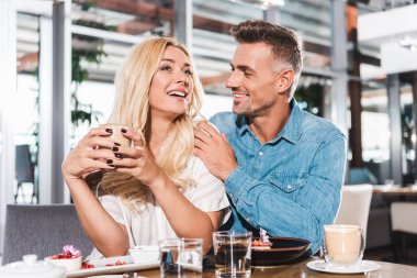 boyfriend hugging laughing girlfriend and she holding cup of coffee at table in cafe