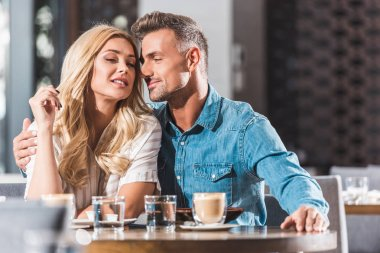 affectionate couple cuddling at table in cafe during date