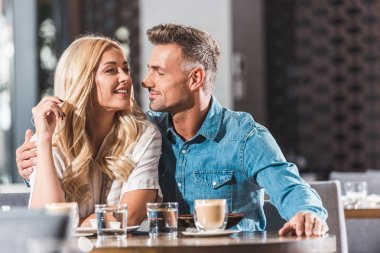 happy romantic couple hugging at table in restaurant