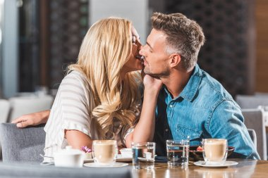 Affectionate romantic couple kissing at table in cafe stock vector