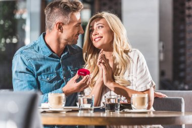 handsome boyfriend proposing happy girlfriend and holding red ring box in cafe