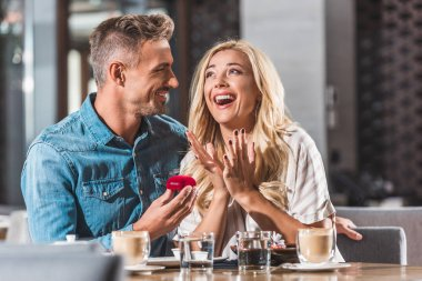 yakışıklı erkek şok el kız ve holding yüzük kutusu kafede öneriyor