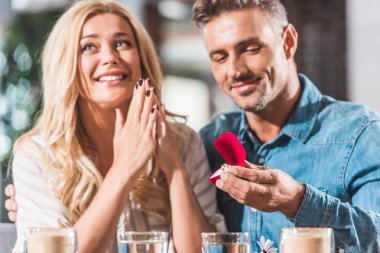 handsome boyfriend proposing happy girlfriend and showing ring in cafe
