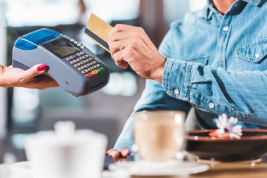 cropped image of man paying with credit card in cafe