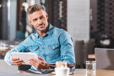 handsome man holding tablet in cafe and looking away