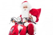 Fotografie santa claus in costume holding christmas sack and riding on scooter isolated on white background