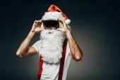Fotografie Santa claus adjsuting očití svědkové izolované na šedém pozadí