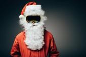 Porträt des Weihnachtsmannes in Skimaske und Windjacke, der isoliert auf grauem Hintergrund steht