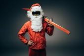 Weihnachtsmann in Skimaske und Windjacke mit Skiern über der Schulter und mit der Hand in der Taille isoliert auf grauem Hintergrund stehend