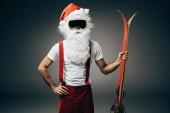 ernsthafter Weihnachtsmann in Skimaske, der mit der Hand auf der Taille steht und die Skier isoliert auf grauem Hintergrund hält
