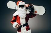 ernste Weihnachtsmann in Skimaske stehend mit Snowboard über der Schulter isoliert auf grauem Hintergrund
