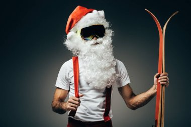 sporty santa claus in ski mask standing skis isolated on grey background