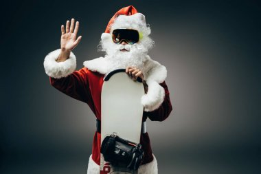 santa claus in ski mask standing with snowboard and waving by hand isolated on grey background