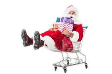 shocked santa claus holding pile of gift boxes in trolley isolated on white background