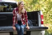 krásná šťastná žena sedí v kufru vyzvednout auto venku