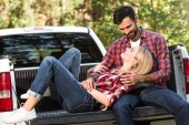 selective focus of woman laying on boyfriend knees on car trunk outdoors