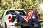 Fotografie lächelnde junge Frau Handauflegen Freund Knie im Kofferraum eines Autos im freien