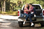 Fotografie side view of young couple embracing each other and looking at each other on car trunk outdoors