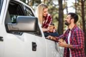 Veselý mladý pár s papírové šálky kávy poblíž vyzvednout auto venku