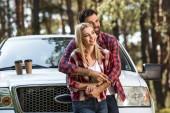 Selektivní fokus mladík objímá přítelkyni poblíž vyzvednout auto s šálky s kávou na kapoty venku