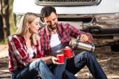Fotografie šťastný mladý muž si naléval kávu přítelkyni Cup z termosky poblíž auto venku