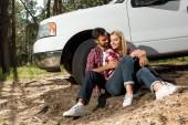 mladý pár sedící na zemi a všeobjímající poblíž vyzvednout auto venku