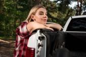 portrét atraktivní mladé ženy při pohledu na fotoaparát poblíž vyzvednout auto venku