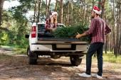 mladý pár v santa klobouky načítání vánoční strom v kufru auta v lese