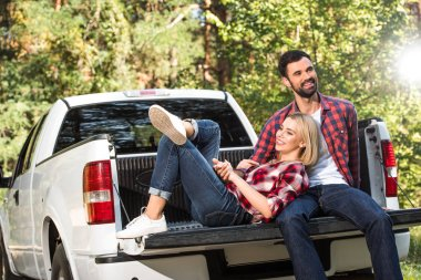 smiling young woman laying on boyfriend knees on car trunk outdoors