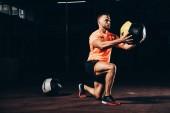 hezký sportovní sportovec provádění výpad s medicinbal v tmavých tělocvičně