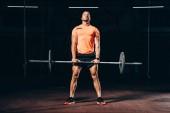 Fotografia uomo atletico bello risolve con il barbell in ginnastica scuro e che osserva in su