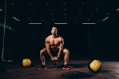 Photo handsome athletic bodybuilder doing squats with kettlebell in dark gym