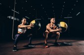 Fotografie athletic sportsman and sportswoman exercising with medicine balls together in dark gym