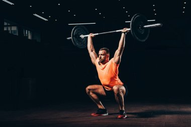 attractive athletic man working out with barbell in dark gym