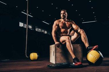 shirtless athletic sportsman sitting on cube in dark gym