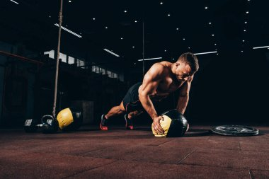 handsome fit sportsman doing push ups on medicine ball in dark gym