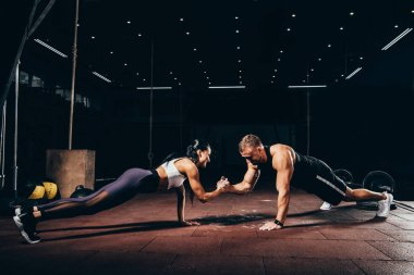 athletic sportsman and sportswoman doing push ups together and holding hands in dark gym
