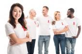 šťastná Asijské žena s překřížením rukou při pohledu na fotoaparát se skupinou lidí v prázdné bílá trička s aids, který povědomí červené stužky stojící izolované na bílém