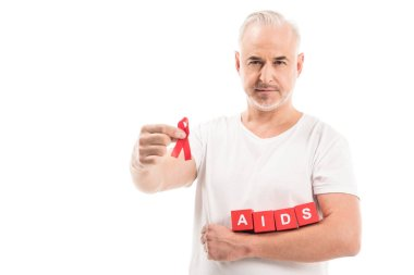 Mature man in blank white t-shirt with aids awareness red ribbon and blocks with AIDS lettering isolated on white stock vector