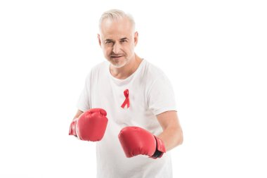 Serious mature man in blank white t-shirt with aids awareness red ribbon and boxing gloves isolated on white, fighting aids concept stock vector