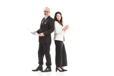successful adult businesspeople with aids awareness red ribbons working with gadgets while standing back to back and looking at camera isolated on white