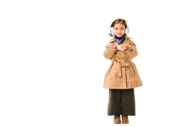 adorable little child in stylish trench coat listening music with headphones and using smartphone isolated on white