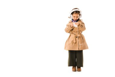 beautiful little child in stylish trench coat listening music with headphones and using smartphone isolated on white