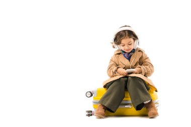 adorable little child in trench coat listening music with headphones and using smartphone while sitting on yellow suitcase isolated on white