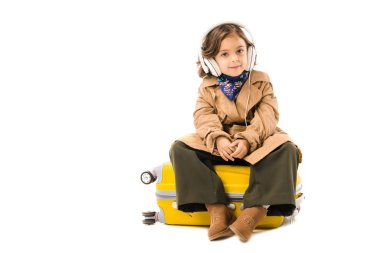 adorable little child in trench coat listening music with headphones and sitting on yellow suitcase isolated on white
