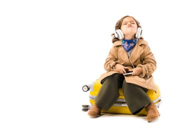 grimacing little child in trench coat listening music with headphones and sitting on yellow suitcase isolated on white