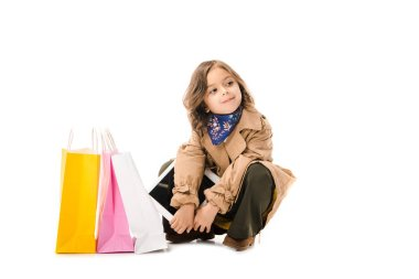 beautiful little child in trench coat sitting on floor with colorful shopping bags isolated on white