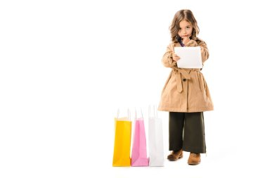 beautiful little child in trench coat with colorful shopping bags using tablet isolated on white