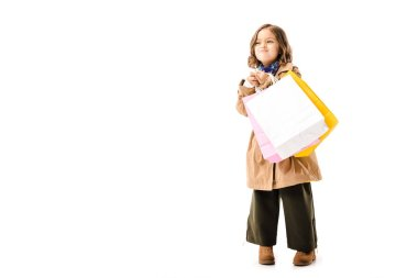 funny little child in trench coat with colorful shopping bags looking away isolated on white